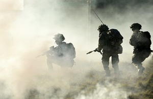 Three armed troops within smoke, two soldiers walking and one soldier crouching down