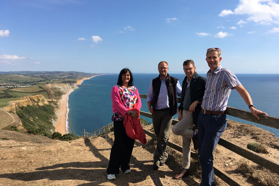 Picture of the review panel leaning against a fence on a cliff edge overlooking the sea