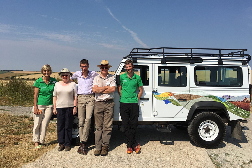 Panel team standing by a car in front of open countryside