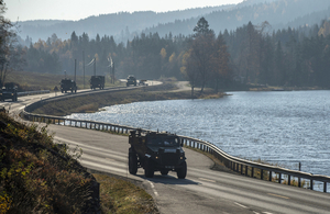 A Foxhound protected patrol vehicle leads a convoy of trucks on a road past a Norwegian lake in the sun