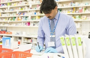 A male pharmacist behind the counter checks a prescription.
