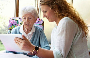 Young woman showing and older woman a digital tablet.