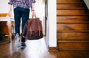 Teenager holding bag, seen from the back, in a house.