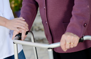 Elderly woman using walker, being assisted by a carer