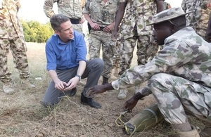 Defence Secretary Gavin Williamson speaks to a Nigerian soldier who is demonstrating how to detect and diffuse an improvised explosive device.