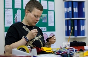 Student at further education college sewing at a table