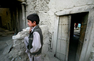 This picture shows a young Afghan boy standing in a yard