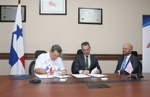 José Gómez Núñez, Director General of the National Customs Authority and the Regional Manager of the British Border Force, Michael Kane sign an agreement with British Ambassador Damion Potter as a witness.
