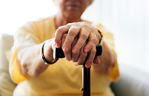 Elderly woman holding a walking stick