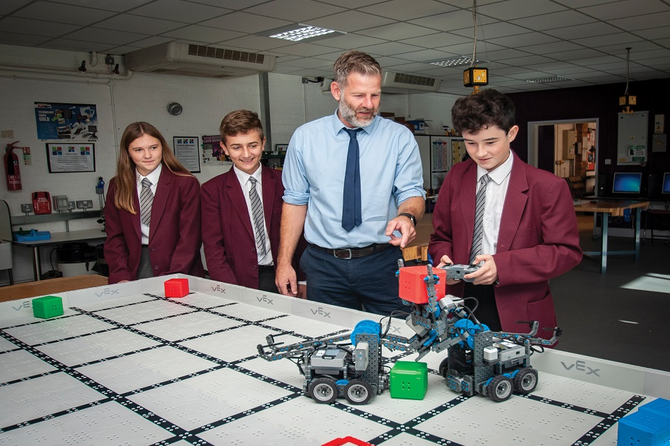 Pupil with remote-controlled model vehicles, standing with two other pupils and teacher