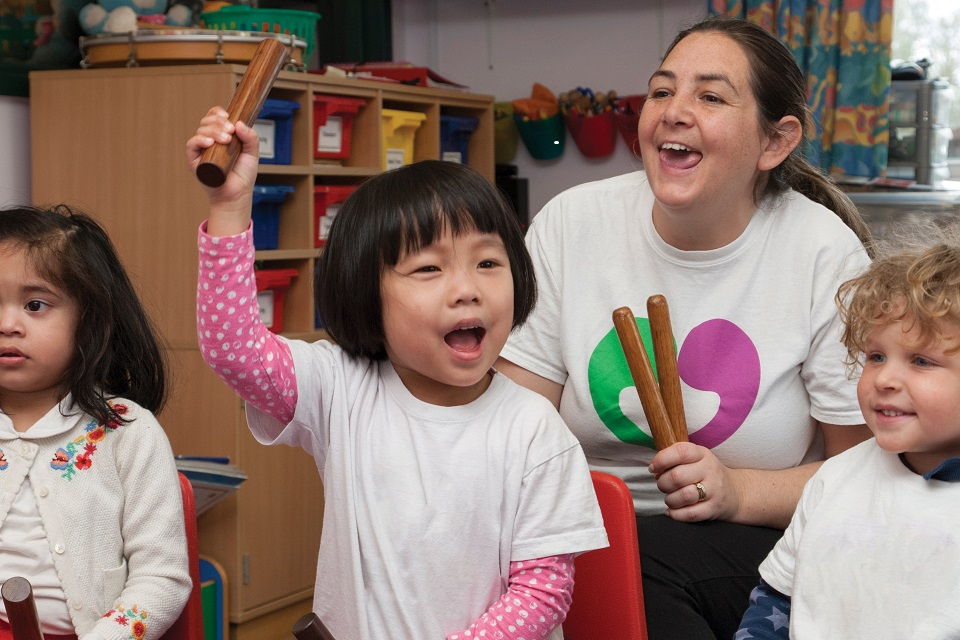 Three young children taking part in musical activity with childcare professional