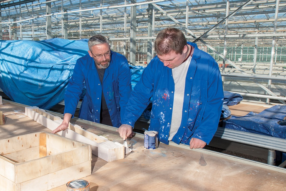 Carpentry student and teacher together in front of workbench