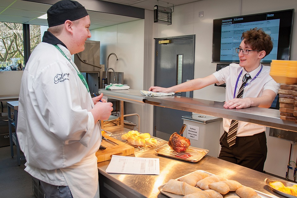 Catering student talking to another student at food bar