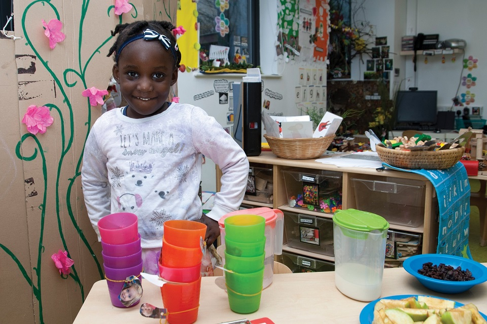 Young girl in nursery standing in front of table with lots of coloured cups