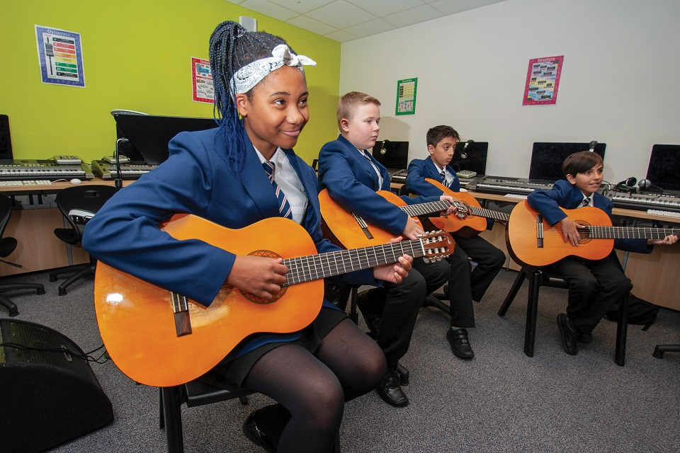 Four secondary school pupils sitting down playing guitars