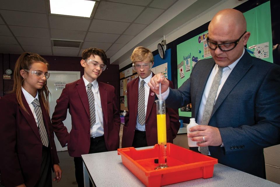 Secondary school pupils wearing safety goggles and watching their teacher pour chemicals into a test tube
