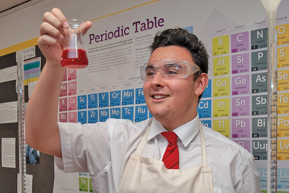Secondary student wearing safety goggles, standing in front of a poster of the Periodic Table and holding up a beaker with red liquid