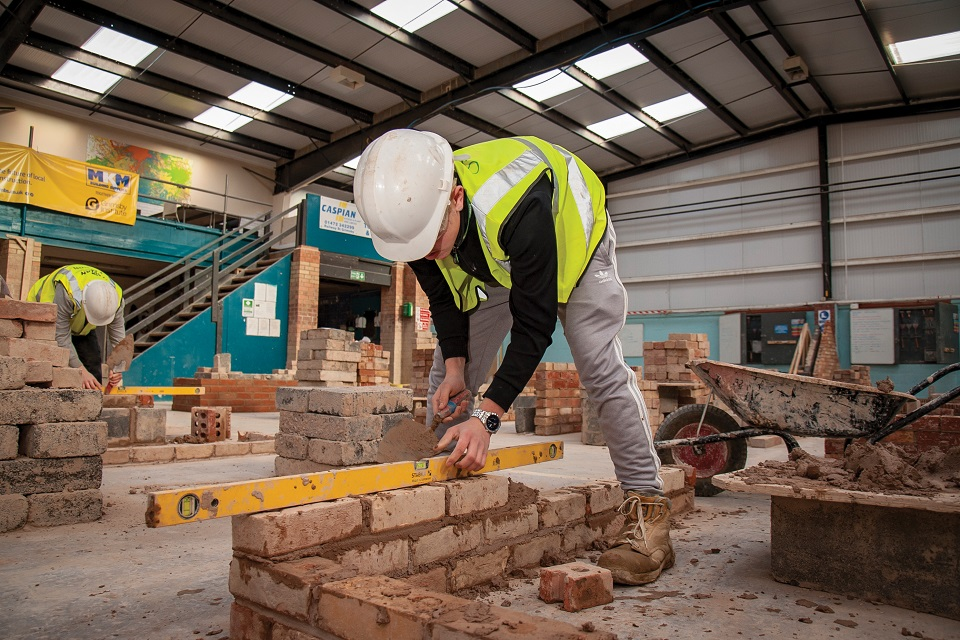 Student in hard hat and high-visibility jacket checking the level of bricklaying