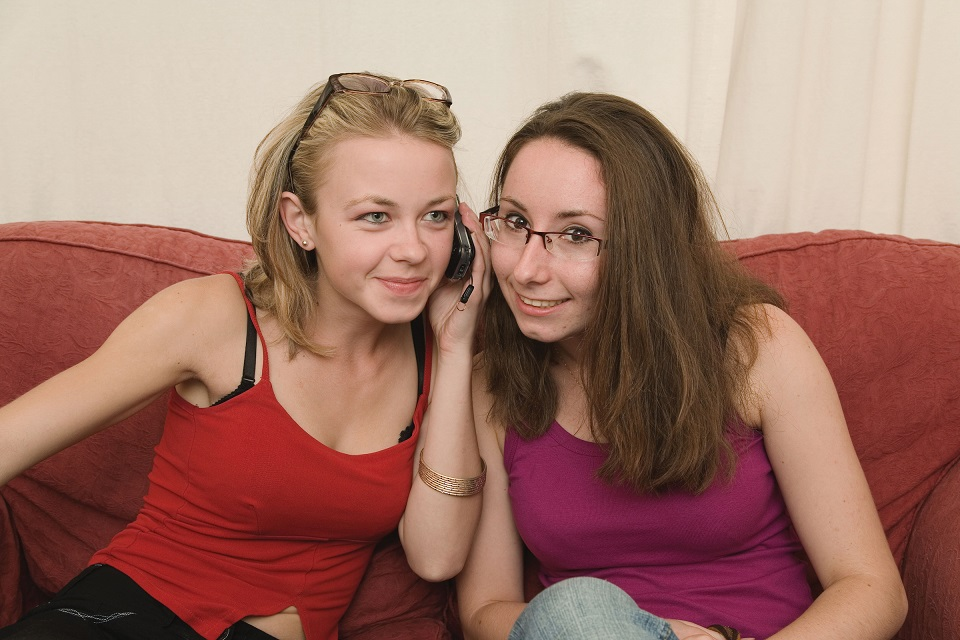 Two teenage girls sitting on a sofa, both listening to the same mobile phone
