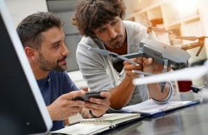 Two technicians work together on a drone via goodluz at Shutterstock