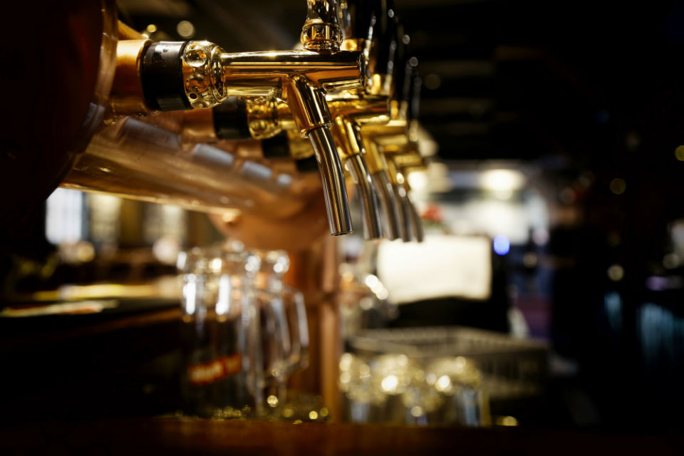 A picture of beer taps on a bar.