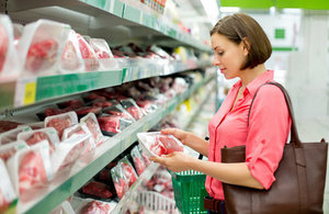 Woman selecting meat at supermarket