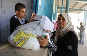 A Palestine refugee woman receives food assistance at the UNRWA Khan Younis Distribution Centre in Gaza in 2016. Picture: UNRWA/Tamer Hamam