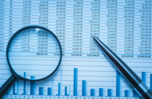 A paper with financial data, a pen and a magnifying glass.