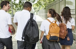 4 teenagers in school uniform walking away into the distance.