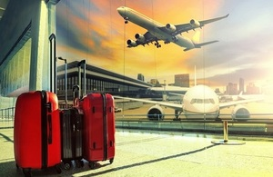 Three red and black suit cases in a airport lounge with an airplane tacking off in the background on a city skyline.