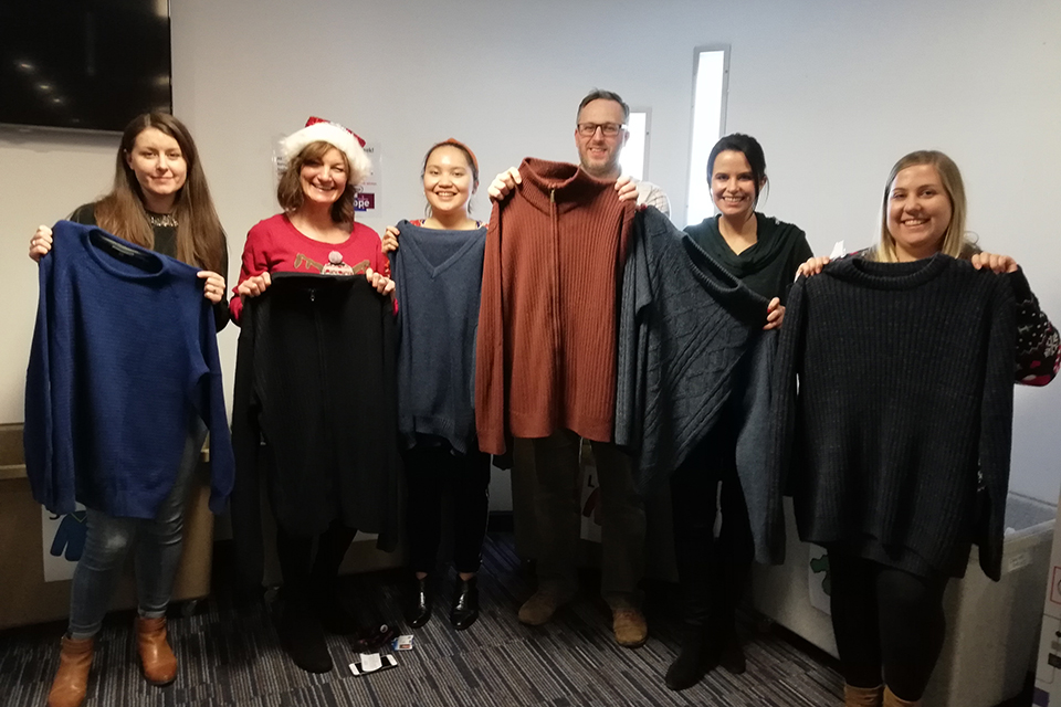Companies House staff holding up some of the jumpers that have been donated