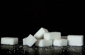 Sugar cubes and some granules of sugar.