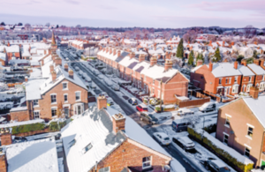 Aerial view of snow covered traditional housing suburbs in England