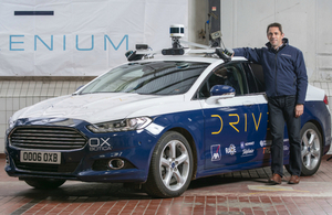 Oxbotica's CEO Graeme Smith with their autonomous vehicles in a warehouse in Oxford