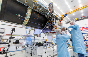 Engineers work on the body of the satellite