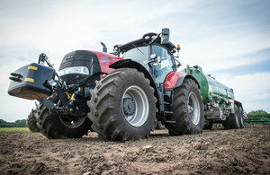 A tractor and liquid manure spreader in a field