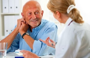 A doctor talks with a senior male patient via Alexander Raths at Shutterstock