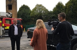 Man being interviewed in front of a fire engine