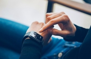 Close up of a smart watch wearer using her device