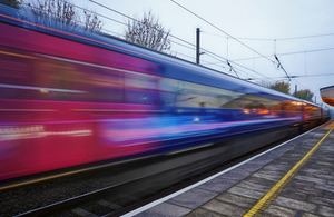 An image of a train traveling past a railway station platform.