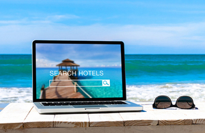 Laptop on a beach with hotel booking website on display
