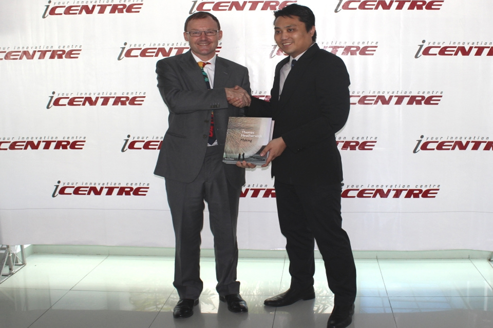 "H.E Rob Fenn presenting Jeremy, Manager for the iCentre, with Thomas Heatherwick's book ""Making"""