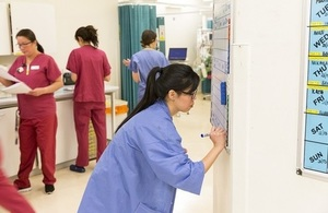 A nurse updating a whiteboard in a hospital.