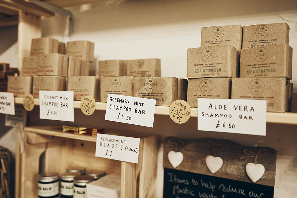 A variety of soaps and shampoo bars on a wooden shelf in the Eco Larder shop.