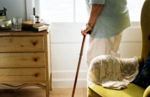 Elderly woman with a crutch.