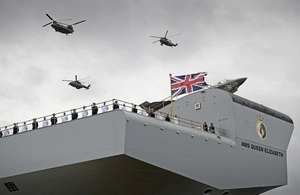 Navy personnel stood on board an aircraft carrier with 3 helicopters and a fast jet