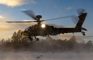 Image of an Apache AH1D helicopter, making a landing in snowy conditions.