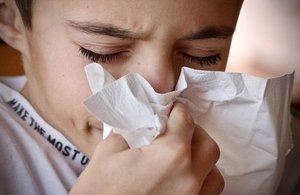 Image of children blowing nose into tissue