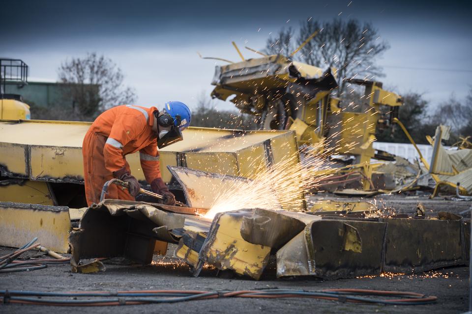 Man in orange protective gear dismantling pieces a crane
