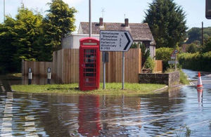 Water up to pavement height with road sign pointing to Winterbourne